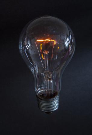 Glühbirne mit gelbem Glühen aus Wolframfaden mit warmem gelbem Glühen auf dunklem Hintergrund dark Standard-Bild