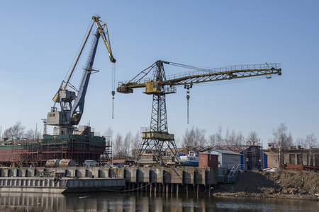 Cranes at the shipyard produced by a large dry cargo barge against a cloudless blue sky