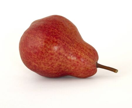 Bright red very ripe appetizing pear with a twig on a white background
