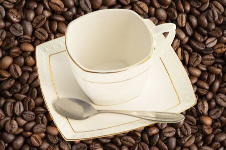 White porcelain Cup with a teaspoon for sugar and saucer on the background of scuffed brown beans fragrant Brazilian coffee 版權商用圖片