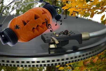 A spinning vinyl disc on a music player with a pumpkin in headphones notes and a spider for Halloween 版權商用圖片
