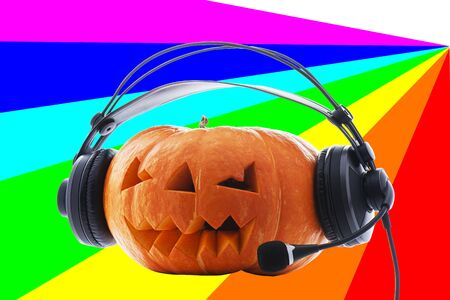 Funny with carved eyes nose mouth pumpkin in headphones and on the background of rainbow colors for Halloween 版權商用圖片