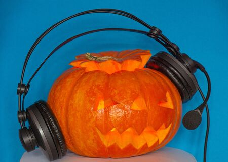 On a blue background orange for the holiday of Halloween pumpkin listens to music on the popular radio with headphones 版權商用圖片