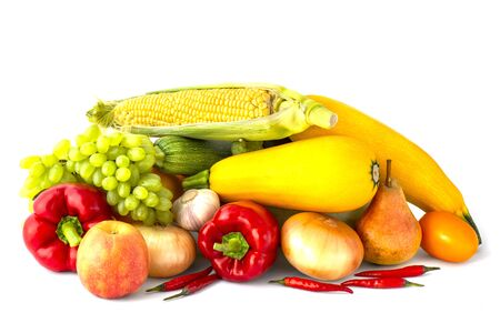Vegetable set of grapes onions bell peppers garlic heads pink tomato chili peppers zucchini and corn cob Apple and pear on a white background