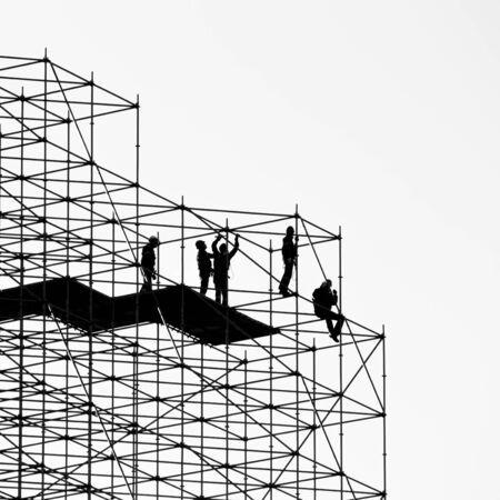 Five construction workers building a metallic scaffold
