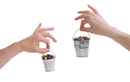 Male and female hands with gems in buckets Фото со стока