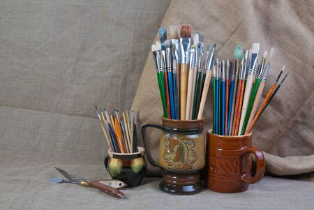 palette knife: Brushes and palette knife in a stein on canvas background