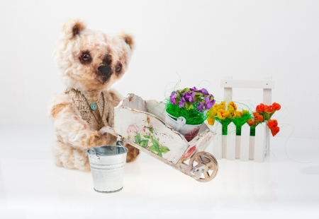 Toy teddy bear to plant flowers on a gray background photo