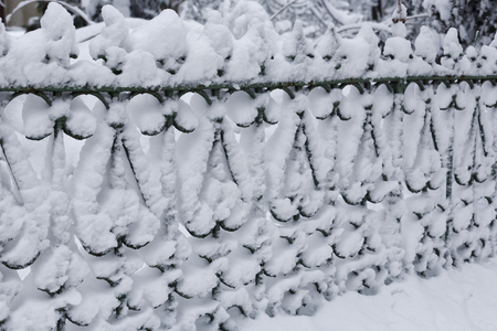 Photo of a city iron fence under the cover of snow. The fence is completely marked by snowdrifts.