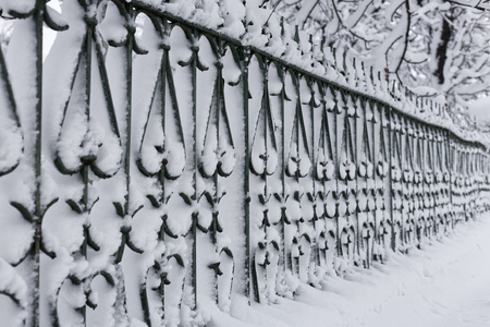 Photo of a city iron fence under the cover of snow. The fence is completely marked by snowdrifts. 版權商用圖片 - 94232793