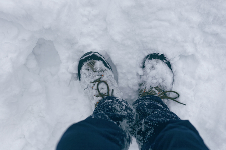 Photo of human feet in the snow in snow-covered boots with an empty white snowy background. View from above. 免版税图像