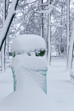 Park sculpture in winter. Photo of a flowerpot on a high pedestal covered with snow
