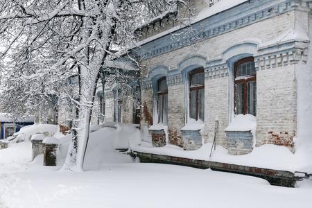 Foto eines Winterstadtbilds. Alte Architektur unter tiefen Schneeverwehungen. Türen und Fenster. Standard-Bild - 94232829