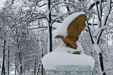Park sculpture in winter. Photo of a bronze eagle with snow
