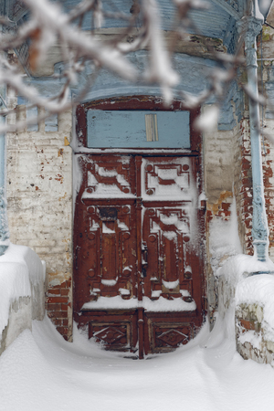 Photo of a winter cityscape. Old architecture under deep snowdrifts. Doors and windows.