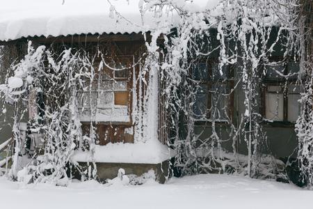Foto eines Winterstadtbilds. Alte Architektur unter tiefen Schneeverwehungen. Türen und Fenster. Standard-Bild - 94252739