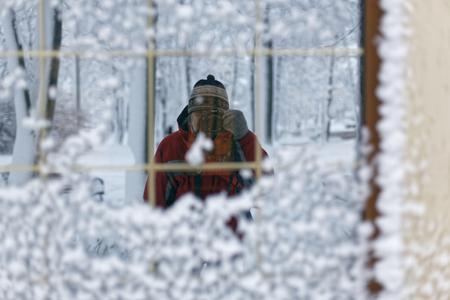 겨울 풍경입니다. 건물의 거울 창에서 자신을 촬영하는 남자의 사진 눈으로 덮여있다.
