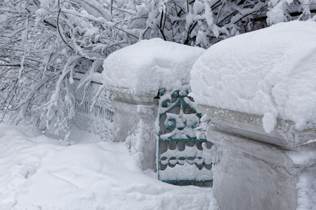 Photo of a winter city landscape with a snow-covered gate and tree branches 版權商用圖片 - 94232804