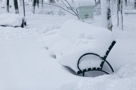 Ein Foto einer Bank in einem Winterpark. Eine leere, einsame Bank, gekennzeichnet von einer Schneeverwehung. Standard-Bild - 94252760