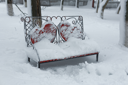 A photo of a bench in a winter park. An empty, lonely bench marked by a snowdrift. Фото со стока