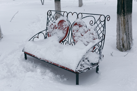 A photo of a bench in a winter park. An empty, lonely bench marked by a snowdrift. 版權商用圖片 - 94232808