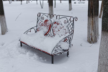 A photo of a bench in a winter park. An empty, lonely bench marked by a snowdrift. 版權商用圖片 - 94232809