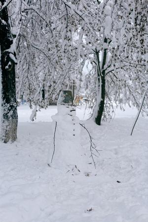 나무와 겨울 풍경의 배경에 눈사람의 사진. 그의 머리에 양동이와 재미 있은 눈사람