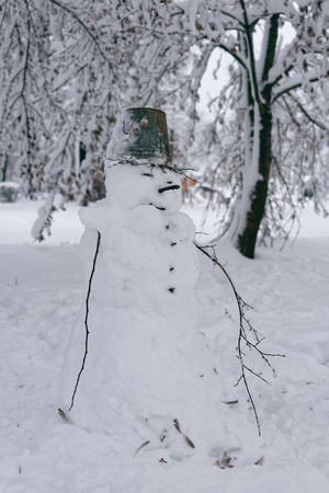 Photo of a snowman on a background of a winter landscape with trees. A funny snowman with a bucket on his head 版權商用圖片 - 94232810