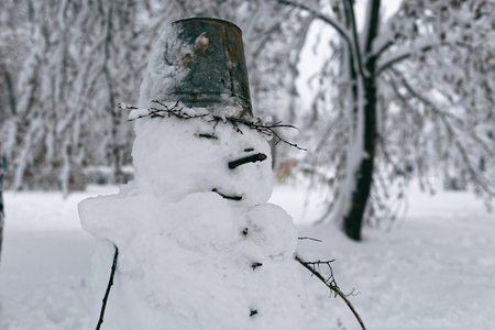 Photo of a snowman on a background of a winter landscape with trees. A funny snowman with a bucket on his head