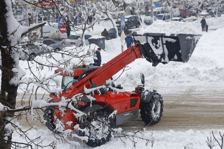 Realistic photography of snow-removing machinery. Excavator clears the road in the city from snow drifts. 版權商用圖片 - 94232812