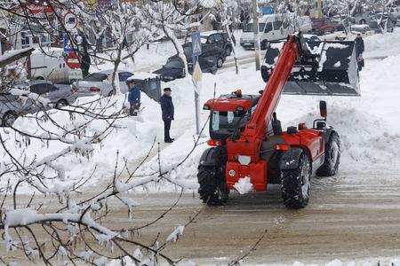 눈 제거 기계의 현실적인 사진. 굴 삭 기는 눈이 내리는에서 도시의 도로를 지 웁니다.