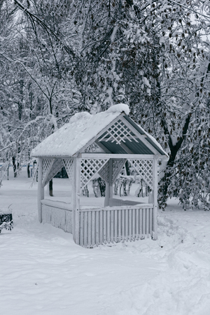 Winter landscape with a gazebo. Photo of a snow-covered park with a white wooden gazebo