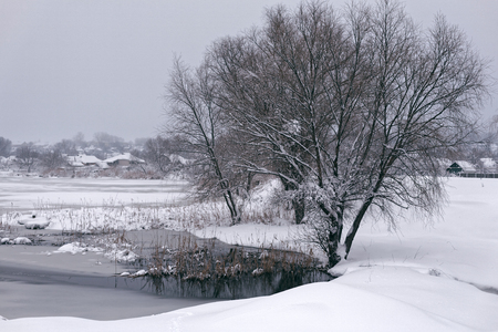 Photo of a winter landscape with a pond. A lot of snow, big snowdrifts, cloudy. 版權商用圖片 - 94232817