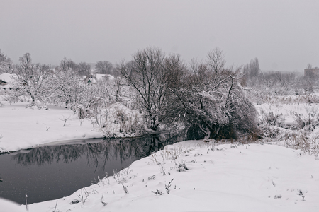 Photo of a winter landscape with a pond. A lot of snow, big snowdrifts, cloudy.