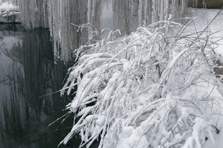Photo of a winter landscape with a pond. A lot of snow, big snowdrifts, cloudy. The trees are low above the water. 版權商用圖片 - 94226438