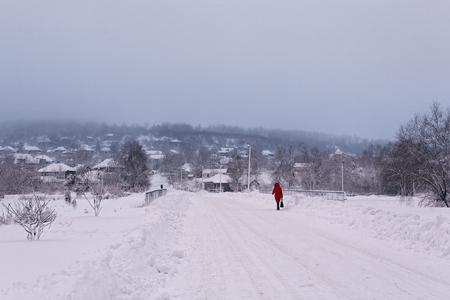 태양이 매우 낮은 아침 일찍 사진 겨울 아침. 도 및 빨간색에서 걷는 남자 농촌 눈 덮인 풍경.