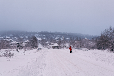 Photo winter morning early in the morning when the sun is very low. A rural snowy landscape with a road and a walking man in red. Stok Fotoğraf