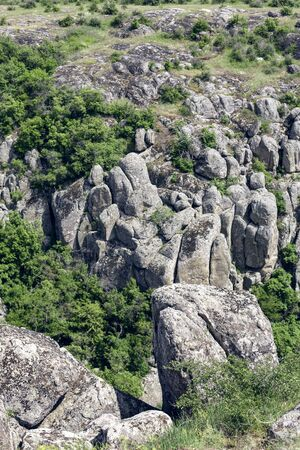 Photo landscape Aktovskogo canyon in Ukraine. Granite rocks overgrown with green trees. Rocky coast. 免版税图像