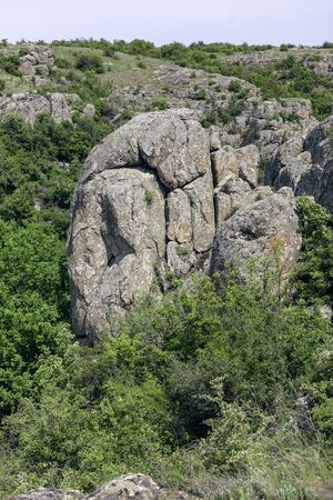 Photo landscape Aktovskogo canyon in Ukraine. Granite rocks overgrown with green trees. Rocky coast. Standard-Bild - 128876019