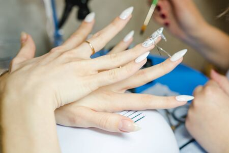 Manicure. The woman cleans and paints nails. The woman processes nails on hands a varnish. Shelak. Gel, a varnish, placing acryle on nails. Salon for manicure.