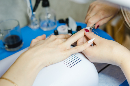 acryle: Manicure. The woman cleans and paints nails. The woman processes nails on hands a varnish. Shelak. Gel, a varnish, placing acryle on nails. Salon for manicure.