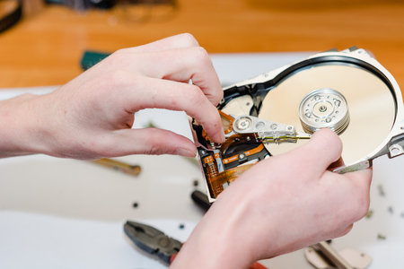 The man repairs a hard drive. Service for repair of kopyyuterny technique.
