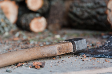splitting: Axe and firewood. The axe lies near firewood. The axe for splitting of a tree.