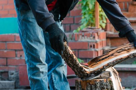 splitting: Splits firewood the axe. The man splits the axe wood. Firewood for the furnace.