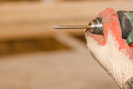 The man twists the screw. Electronic screwdriver. Screws in the hands