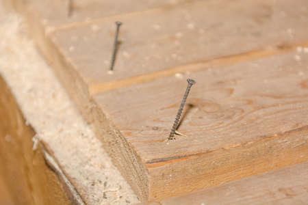 Screws in the boards. Screws in the board on the floor. The man twists the screws.