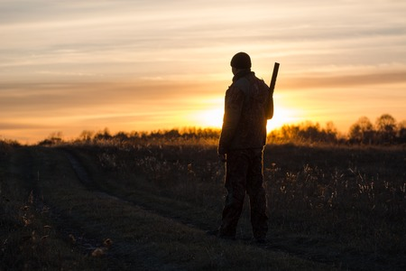 Hunter in backlight. Hunter at sunset. The shadow of the hunter. The man in the field.