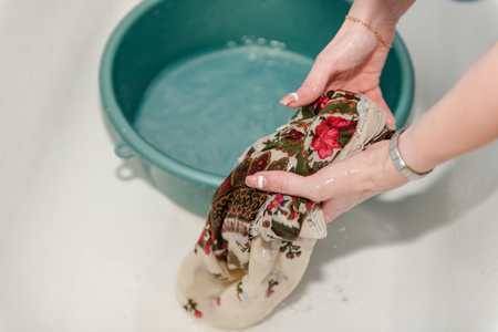Handwash. A woman is washing her hands. Washing clothes. Wet clothes.