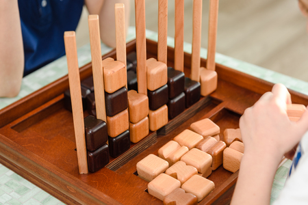 Children play a logic game with wooden cubes. Board game. Educational game for children Banque d'images - 116472537