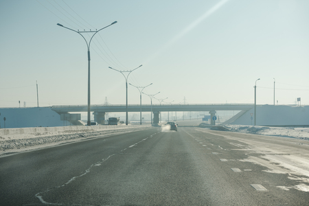 The road in winter. Asphalt road in winter. Road under the snow. Russian roads.